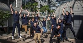 Photo des 11 personnes de l'équipe Koovea habillées du polo brandé et qui sautent dans un patio.